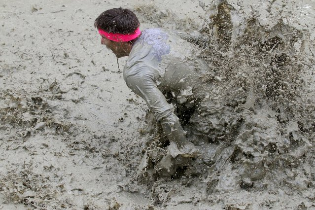 A participant of the Wild Sau Dirt Run 2015 makes his way through the mud  in Obertriesting, Lower Austria, Austria, Saturday, April 4, 2015. (Photo by Ronald Zak/AP Photo)