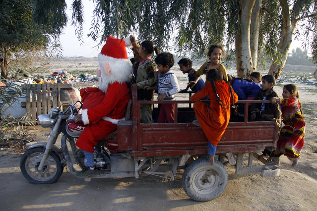 A man dressed in a Santa Claus outfit touring a popular neighbourhood on the outskirts of the Iraqi central city of Najaf, takes children on a ride in a tuktuk on December 25, 2018. (Photo by Haidar Hamdani/AFP Photo)