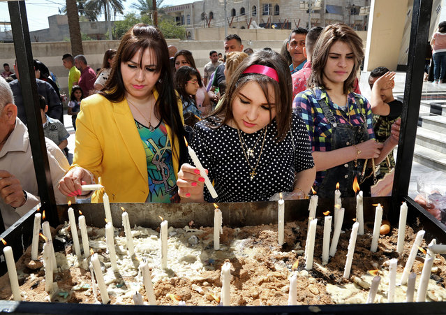 Iraqis women light candles after the Palm Sunday service at Lady Deliverance Church in Baghdad, Iraq, Sunday, April 5, 2015. Christians across the world are celebrating Easter, commemorating the day followers believe Jesus was resurrected in Jerusalem over 2,000 years ago. (Photo by arim Kadim/AP Photo)