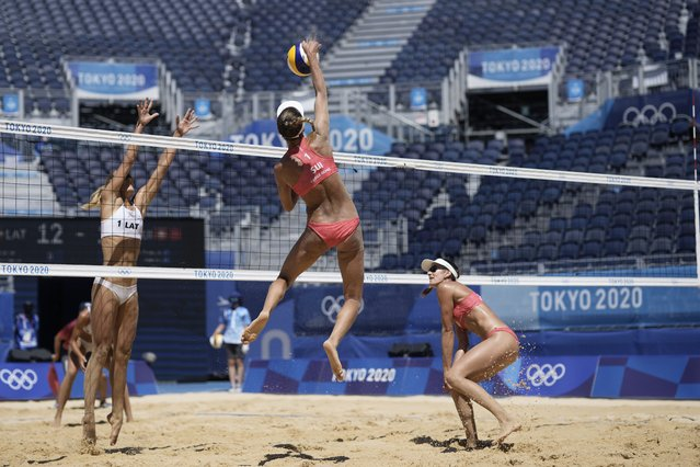 Anouk Verge-Depre, top right, of Switzerland, takes a shot as teammate Joana Heidrich, right, watches while Tina Graudina, of Latvia, defends during a women's beach volleyball Bronze match at the 2020 Summer Olympics, Friday, August 6, 2021, in Tokyo, Japan. (Photo by Petros Giannakouris/AP Photo)