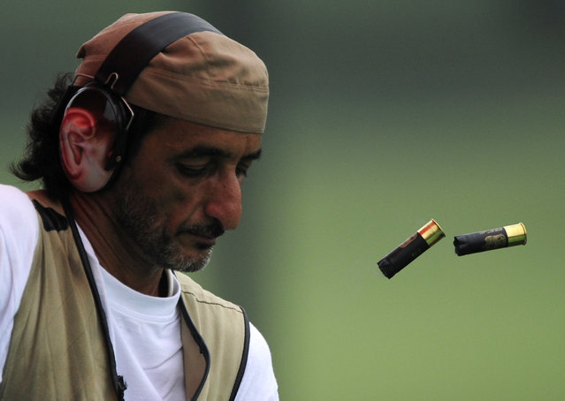 Ahmed Almaktoum of the UAE unloads his shotgun during the qualifying round of the men's trap competition of the shooting event at the Beijing 2008 Olympic Games. August 2008. (Photo by Desmond Boylan/Reuters)