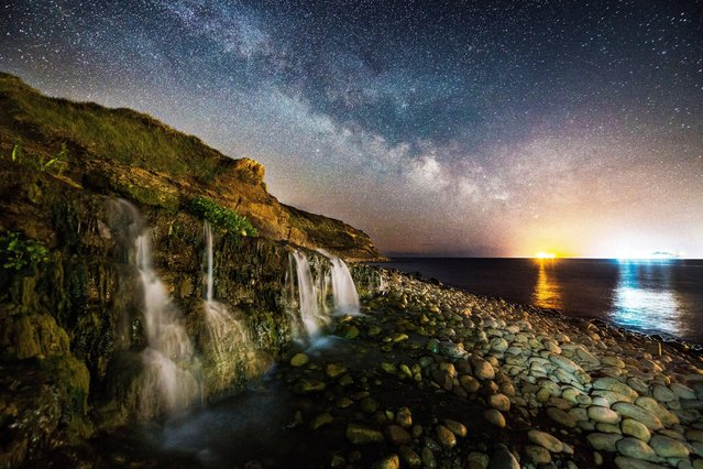The Milky Way glows in clear skies over Osmington Mills, Dorset in United Kingdom on May 5, 2021, where a 2.4 metre skull fossil from a pliosaur was found in 2019. (Photo by Graham Hunt/Alamy Live News)