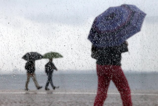People, photographed through a window with raindrops, shelter under umbrellas against the rain as they walk near the Tagus riverbank in Lisbon, Wednesday, April 8, 2015. The city promenade is a popular riverside walking path where people stroll or enjoy fishing. (Photo by Francisco Seco/AP Photo)