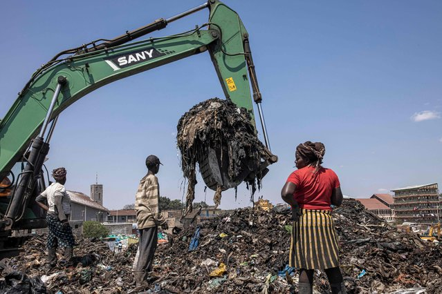 An excavator moves garbage at a dumping site near Dandora informal settlement in Nairobi, Kenya, on July 24, 2021. The Environment and Land Court ordered the closing of the Dandora dumpsite within six months and directed Nairobi Metropolitan Services (NMS) to establish a new dumping site that will follow environmental guidelines. (Photo by Patrick Meinhardt/AFP Photo)