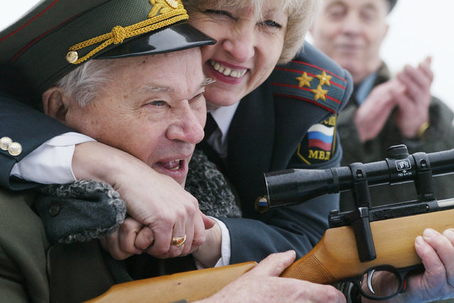 Police officer Tatiana Osetrova congratulates Mikhail Kalashnikov, the father of the world's most popular assault rifle, November 23, 2002 in Izhevsk,1000 East km. from Moscow. (Photo by Oleg Nikishin/Getty Images)