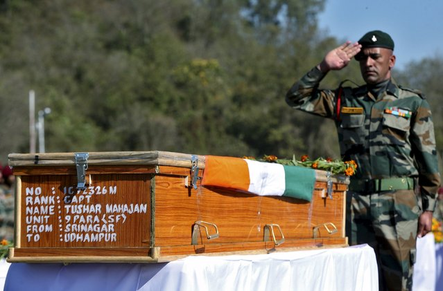 An Indian army officer salutes at the coffin containing the body of Tushar Mahajan, an army officer who was killed in a gunbattle, during his wreath laying ceremony in Udhampur, north of Jammu, February 22, 2016. (Photo by Mukesh Gupta/Reuters)