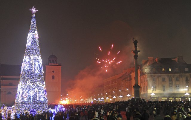 People gather during the New Year's Eve celebration in the Old Town in Warsaw, Poland, Wednesday, January 1, 2014. (Photo by Alik Keplicz/AP Photo)