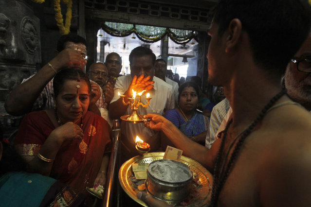 """Devotees perform rituals and offer prayers at a temple of Hindu God Muruga on """"Puthandu"""" in Chennai, India, Tuesday, April 14, 2015. Puthandu, or Tamil New Year, is celebrated by Tamils living across the world. (Photo by Arun Sankar A./AP Photo)"""