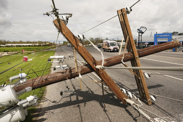 Ambulances pass by a downed power pole after Hurricane Ida moved through Monday, August 30, 2021, in LaPlace, La. (Photo by Steve Helber/AP Photo)