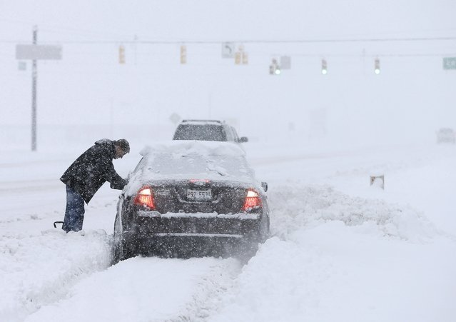 A motorist helps dig out a driver stuck in a snow drift Sunday, January 5, 2014, in Zionsville, Ind. Snow that began in parts of Indiana Saturday night picked up intensity after dawn Sunday with several inches of snow on the ground by midmorning and more on the way. (Photo by Darron Cummings/AP Photo)