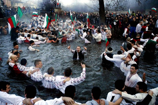 Men dance in the icy waters of the Tundzha river during a celebration for Epiphany Day in the town of Kalofer, Bulgaria, on January 6, 2014. It is believed that the ritual will bring health throughout the new year.  (Photo by Stoyan Nenov/Reuters)