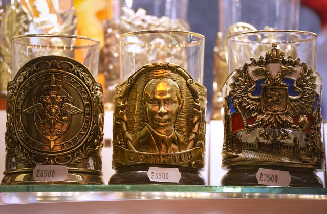 A cup holder depicting Russian President Vladimir Putin, centre, among others is displayed for sale at a street souvenir shop in St. Petersburg, Russia, Wednesday, September 8, 2021. (Photo by Dmitri Lovetsky/AP Photo)