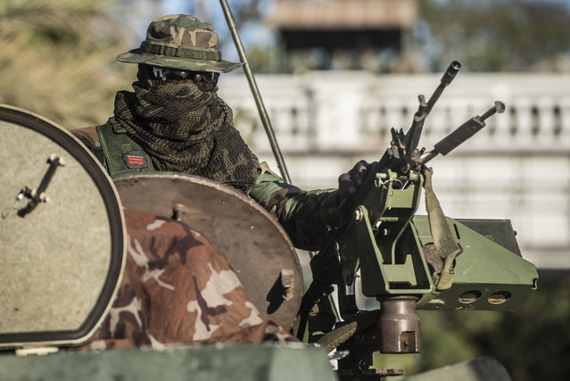 An ECOWAS Senegalese soldier guards the State House entrance in Banjul, Gambia, Wednesday January 25, 2017. Gambia's new President Adama Barrow will arrive in the country on Thursday, a week after he was sworn into office in neighboring Senegal, officials with the new government confirmed Wednesday. (Photo by Sylvain Cherkaoui/AP Photo)