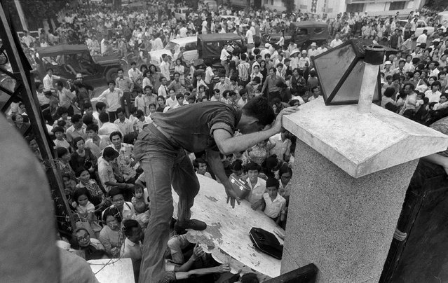 "In this April 29, 1975, file photo, South Vietnamese civilians try to scale the 14-foot wall of the U.S. embassy in Saigon, trying to reach evacuation helicopters as the last Americans departed from Vietnam. More than two bitter decades of war in Vietnam ended with the last days of April 1975. Today, 40 years later, former Associated Press correspondent Peter Arnett has written a new memoir, ""Saigon Has Fallen"", detailing his experience covering the war for The AP. (Photo by AP Photo)"