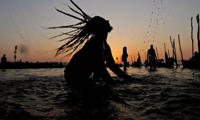 """A Naga Sadhu, or Hindu holy naked man, takes holy dips at Sangam, confluence of Hindu holy rivers of Ganges, Yamuna and the mythical Saraswati, for a ritual dip, on the auspicious occasion of """"Basant Panchami"""" at the annual traditional fair of Magh Mela in Allahabad, India, Tuesday, February 4, 2014. Basant Panchami, the fifth day of spring is celebrated by worshipping Hindu Goddess of knowledge and wisdom, Saraswati. (Photo by Rajesh Kumar Singh/AP Photo)"""