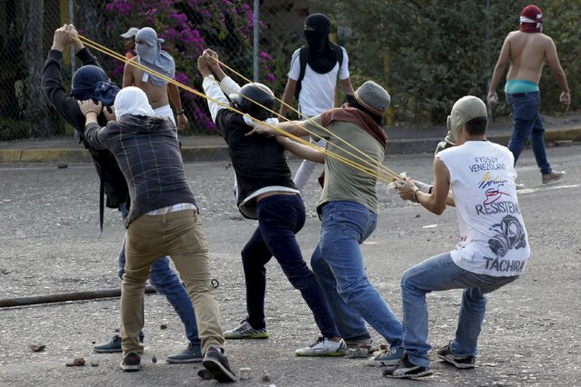 Student demonstrators use a slingshot to throw rocks at police during a protest against Venezuelan President Nicolas Maduro's government in San Cristobal, Venezuela, March 10, 2016. (Photo by Carlos Eduardo Ramirez/Reuters)