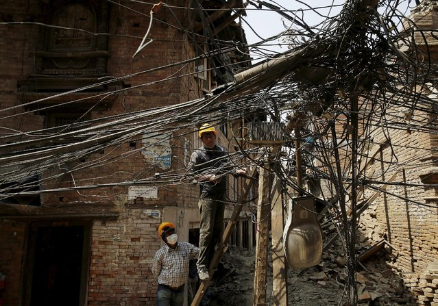 Engineers examine power lines brought down by the April 25 earthquake in Bhaktapur, Nepal, May 6, 2015. (Photo by Olivia Harris/Reuters)