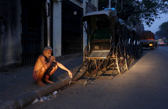 A man brushes his teeth with a neem twig early morning next to a row of hand-pulled rickshaws in Kolkata, India, March 12, 2016. (Photo by Rupak De Chowdhuri/Reuters)