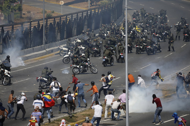 Opponents to Venezuela's President Nicolas Maduro confront loyalist Bolivarian National Guard troops firing tear gas at them, outside La Carlota military airbase in Caracas, Venezuela, Tuesday, April 30, 2019. Venezuelan opposition leader Juan Guaidó took to the streets with activist Leopoldo Lopez and a small contingent of heavily armed troops early Tuesday in a bold and risky call for the military to rise up and oust socialist leader Nicolas Maduro. (Photo by Fernando Llano/AP Photo)