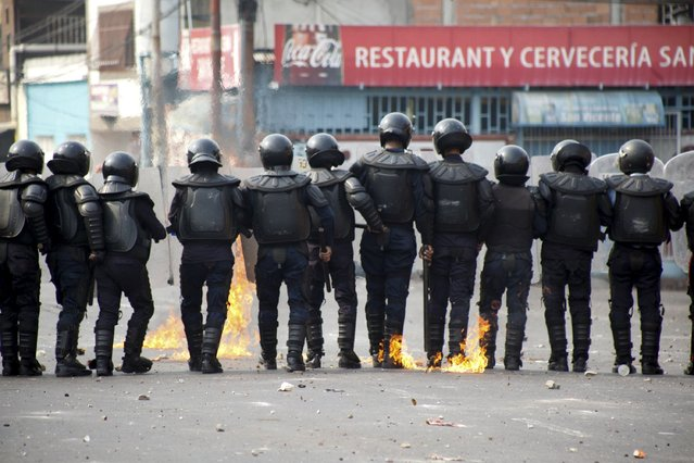 Police officers walk near a fire while they clash with demonstrators during a protest against the increase in the price of public transport in San Cristobal March 29, 2016. (Photo by Carlos Eduardo Ramirez/Reuters)