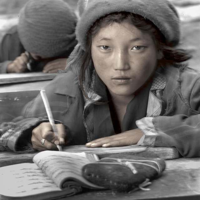 """Yeshi was practicing her Tibetan script on a painted board in this small village school. I was amazed by the quality of her work. It was like some of the finest calligraphy I had seen. Her teacher was a Tibetan who had been educated in a Chinese run university. My interpreter told me that even though the Tibetan language was being taught the content of all their books on history and Tibetan culture were written from a Chinese perspective"". (Phil Borges)"