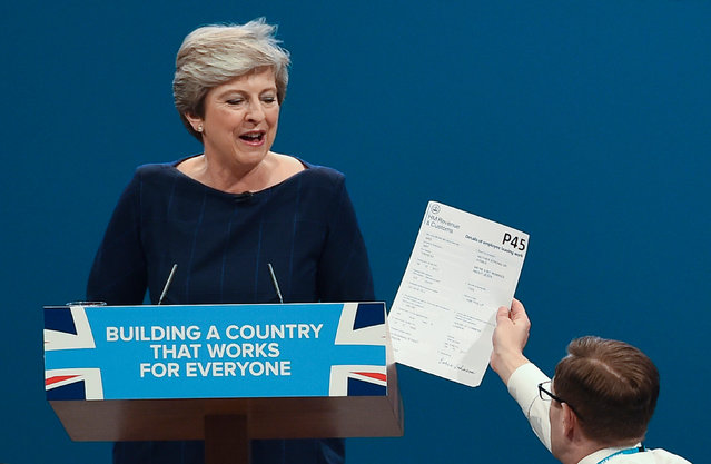Protester Simon Brodkin gives a mock P45 to Theresa May as she delivers her speech on the final day of the Conservative conference in Manchester on 4 October 2017. (Photo by Paul Ellis/AFP Photo)