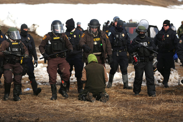 Police detain a man in an attempt to clear the Oceti Sakowin camp in Cannon Ball, North Dakota, U.S., February 23, 2017. (Photo by Stephen Yang/Reuters)