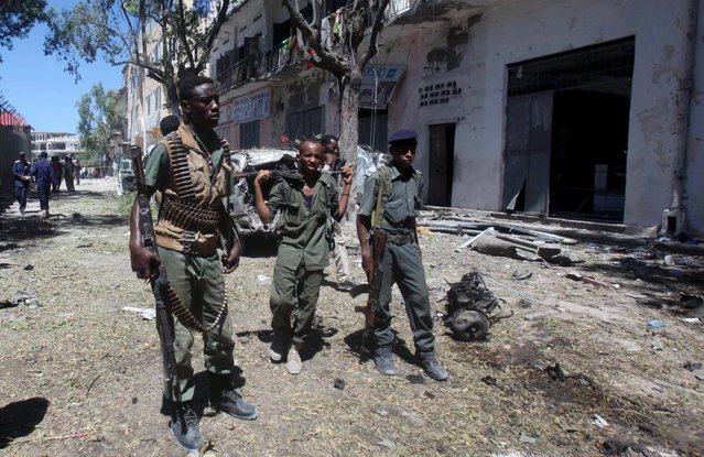 Somali policemen stand near the scene of a car bomb explosion at a local government headquarters that killed five people in Somalia's capital Mogadishu, April 11, 2016. (Photo by Ismail Taxta/Reuters)