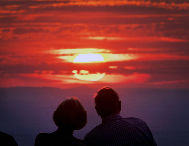 A couple watches the sun go down on top of the Feldberg mountain near Frankfurt, Germany, on a hot Monday, July 30, 2018. (Photo by Michael Probst/AP Photo)