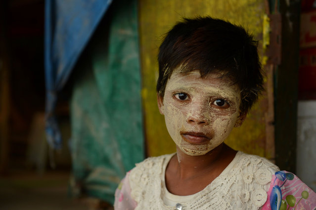 Eight year old Myanmar girl Sable Moe, meaning Jasmine flower and rain, wearing traditional sun protection cosmetic paste looks on from a river bank in Yangon on April 17, 2016, where residents cross by boat to travel to Shwedagon pagoda for special prayers to celebrate the country's traditional New Year following the Thingyan water festival. (Photo by Romeo Gacad/AFP Photo)