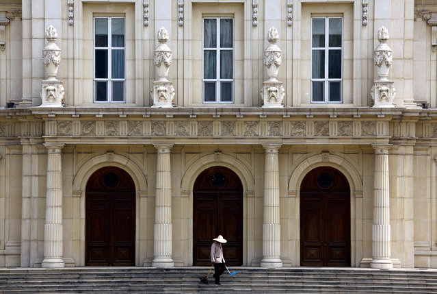 A cleaner works in front of a building that makes up the luxurious Chateau Laffitte Hotel, an imitation of the 1650 Château Maisons-Laffitte by the French architect Francois Mansart, located on the outskirts of Beijing, August 20, 2010. (Photo by David Gray/Reuters)