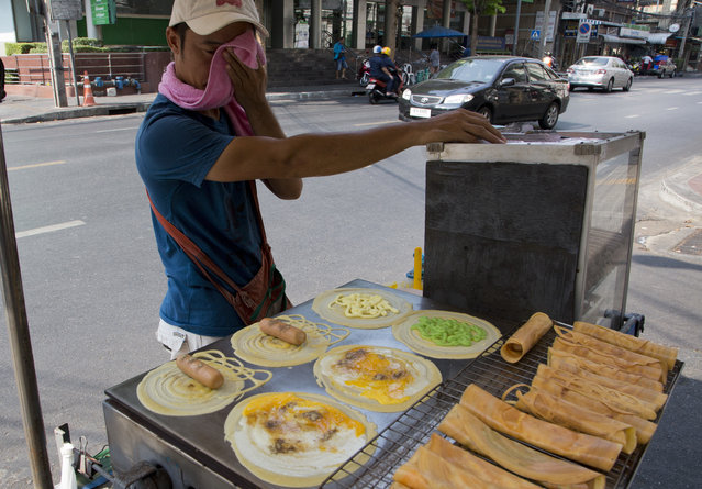 A street vendor wipes the sweat from his face as he cooks food in central Bangkok, Thailand, Wednesday, April 27, 2016. April in Thailand is typically hot and sweaty but this year's scorching weather has set a record for the longest heat wave in at least 65 years. The Department of Disease Control has warned people to beware of food poisoning and other food-related illnesses that typically increase during hot weather when bacteria can thrive on unrefrigerated food. (Photo by Mark Baker/AP Photo)
