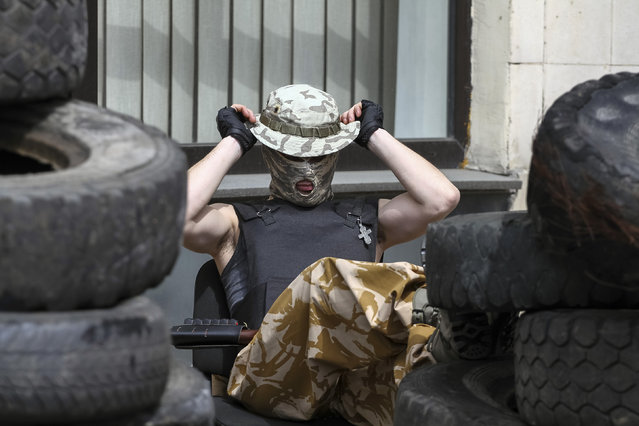 A pro-Russian armed man stands guard outside the mayor's office in Donetsk April 16, 2014. Dozens of masked pro-Russian separatists armed with Kalashnikov assault rifles have seized control of the city hall in the eastern Ukraine city of Donetsk demanding a referendum, a local government spokesman said on Tuesday. (Photo by Reuters)