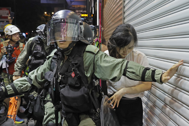 Police detain a girl during a confrontation in Hong Kong on Saturday, August 10, 2019. Hong Kong is in its ninth week of demonstrations that began in response to a proposed extradition law but have expanded to include other grievances and demands for more democratic freedoms. (Photo by Kin Cheung/AP Photo)