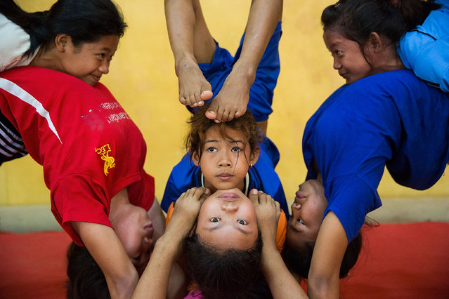 Female circus students practice for a performance  on July 1, 2015 at Phare Ponleu Salpak in Battambang, Cambodia. Phare Ponleu Salpak is an organization providing free education and artistic training to Cambodian children. Students in the organization's circus program often go on to careers performing both internationally and domestically at venues like Phare – The Cambodian Circus in Siem Reap. (Photo by Taylor Weidman/Getty Images)