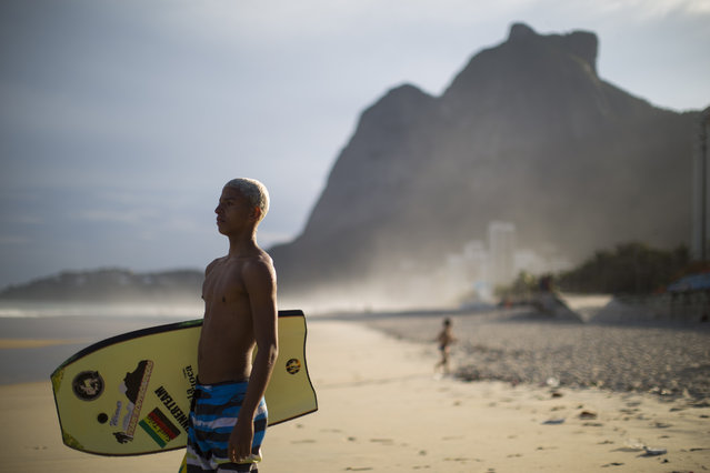 A young bodyboarder from Rocinha watches the waves before surfing at Sao Conrado beach in Rio de Janeiro, Brazil, Wednesday, July 1, 2015. Everyday barefoot boys hustle down the inclined alleyways of the Rio de Janeiro slums they call home, surf boards under their arms. They head to nearby Sao Conrado or Arpoador beach, where they catch waves and momentarily leave their impoverished lives behind. (Photo by Felipe Dana/AP Photo)