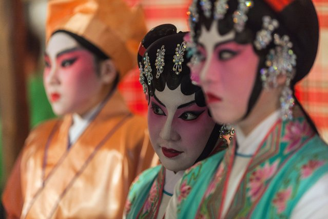 In this picture taken on April 20, 2014, Chinese Cantonese opera singers watch from the side of the stage before their performance during the Tin Hau festival on Lamma Island, an outlying island of Hong Kong. Tin Hau, whose birthday is celebrated this year on April 22, is known as the Goddess of the Sea and maintains high popularity ratings amongst Hong Kongers due to the close association between the territory and the sea – two other sea-faring places, Macau and Vietnam also hold Tin Hau in high-regard. (Photo by Anthony Wallace/AFP Photo)