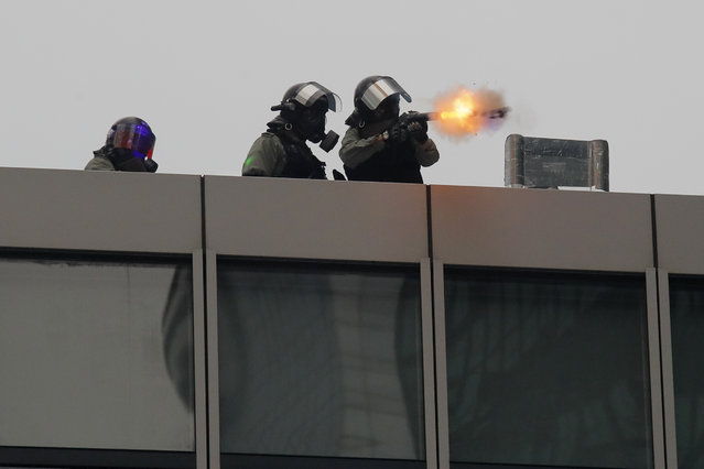 Policemen fire tear gas shells on protestors from the roof of a building in Hong Kong, Saturday, August 31, 2019. Many of the protesters outside Hong Kong government headquarters have retreated as large contingents of police arrive on the streets in what looks like preparation for a clearing operation. (Photo by Kin Cheung/AP Photo)