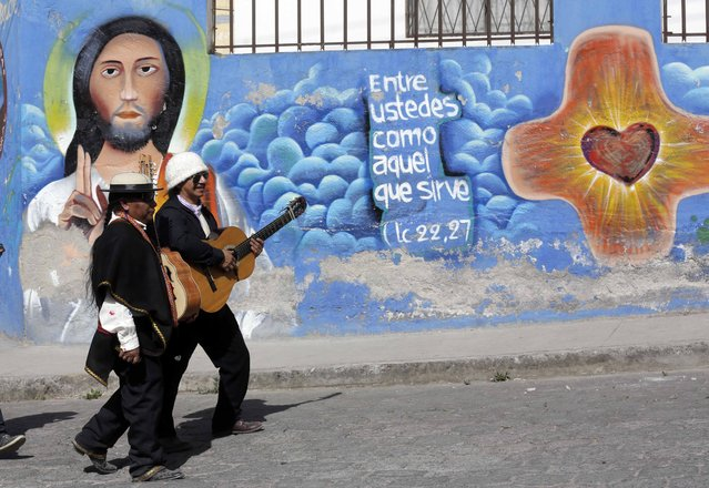 In this June 24, 2015 photo, two musicians walk past a religious mural in Peguche, Ecuador, during the celebrations of the Catholic feast day for St. John the Baptist and the Indian celebration Inti Raymi or Festival of the Sun. While most of the region's native peoples identify themselves as Roman Catholic, some practice syncretic rituals that blend the church's traditional beliefs with native customs. Many Andean people see no contradiction in it. (Photo by Dolores Ochoa/AP Photo)