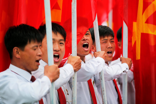 Students carrying party flags shout slogans as they march past North Korean leader Kim Jong Un during a mass rally and parade in the capital's main ceremonial square, a day after the ruling party wrapped up its first congress in 36 years by elevating him to party chairman, in Pyongyang, North Korea, May 10, 2016. (Photo by Damir Sagolj/Reuters)