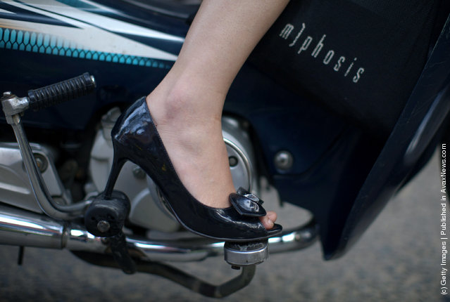 A Vietnamese woman wears high heels while commuting to work on her motorcyle