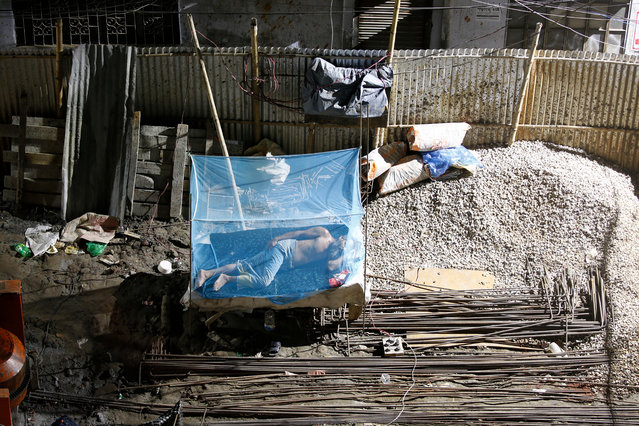 A Bangladeshi man sleep in a construction site as labors carry construction material at mid-night in Dhaka, Bangladesh, 28 June 2019. Dhaka is a one of the most populated cities in the world, built along the Buriganga river, in 2016 the population was 18 million in the greater Dhaka area. (Photo by Monirul Alam/EPA/EFE)