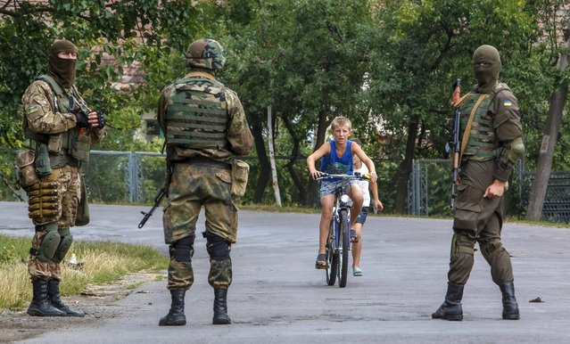 "A local boy rides a bicycle towards Ukrainian government servicemen as they conduct a search for members of Right Sector in the village of Bobovyshche near Mukacheve, Ukraine, July 14, 2015. On Saturday, two people were killed in a firefight between members of the ultranationalist group, Right Sector, and police in the town of Mukacheve in western Ukraine, prompting President Petro Poroshenko to call for all ""illegal groups"" to disarm. (Photo by Reuters/Stringer)"