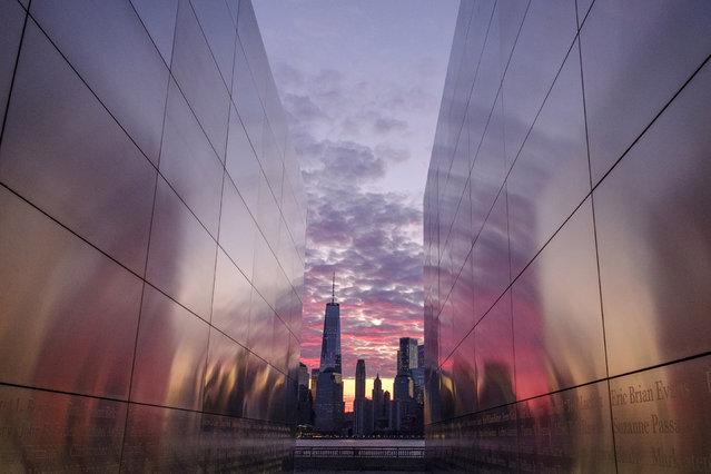 Framed through the Empty Sky Memorial in Jersey City, N.J., sunrise lights up the sky behind the New York City skyline Thursday, April 11, 2019. (Photo by J. David Ake/AP Photo)