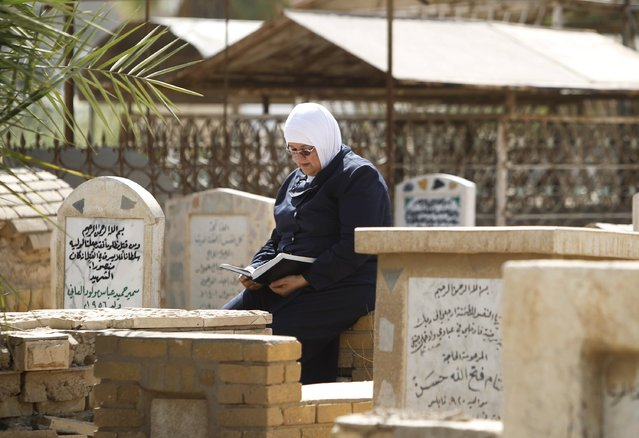A woman reads verses from the Koran as she visits the grave of a relative in a cemetery during Eid al-Fitr celebrations, marking the end of the Muslim fasting month of Ramadan, in Baghdad, July 17, 2015. (Photo by Ahmed Saad/Reuters)