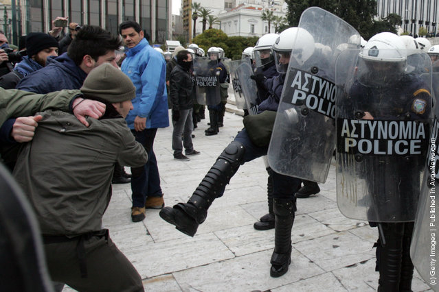 The police clash with protestors during a demonstration involving thousands of Greek civilians