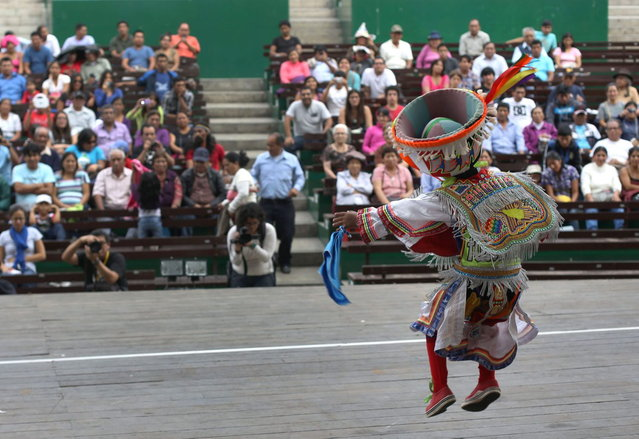 A little scissors dancer Alexis Cule of 7 years old performs during a dance competition in Lima, Peru, Sunday, May 18, 2014. The scissors dance is performed by inhabitants of Quechua villages and communities in the south-central Andes of Peru, and now in urban settings. This competitive ritual dance is performed during dry months coinciding with the main phases of the agricultural calendar. (Photo by Martin Mejia/AP Photo)