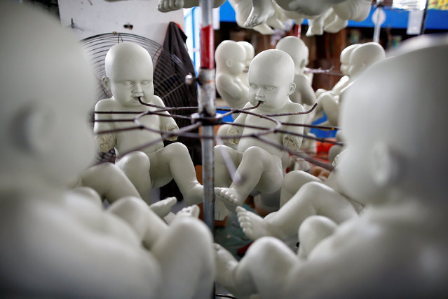 Dolls hang out to dry at Jinhua Partytime Latex Art and Crafts Factory in Jinhua, Zhejiang Province, China, May 25, 2016. (Photo by Aly Song/Reuters)