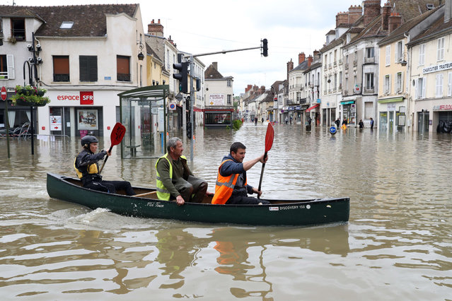 People paddle in a craft in a flooded street on June 1, 2016 in Nemours. Torrential downpours have lashed parts of northern Europe in recent days, leaving four dead in Germany, breaching the banks of the Seine in Paris and flooding rural roads and villages. (Photo by Kenzo Tribouillard/AFP Photo)
