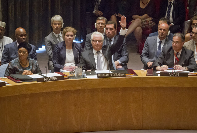 Russian U.N. Ambassador Vitaly Churkin, center, raises his hand to cast a vote to veto a draft resolution in the Security Council that would create a tribunal to prosecute those found responsible for the downing of Malaysia Airlines Flight 17 over eastern Ukraine, Wednesday, July 29, 2015 at U.N. headquarters. (Photo by Bebeto Matthews/AP Photo)